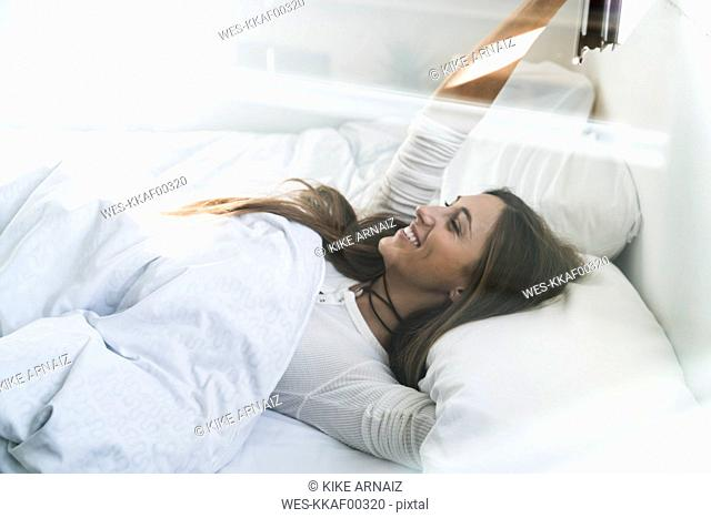 Smiling young woman lying in bed