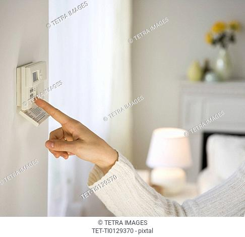 Woman adjusting digital thermostat