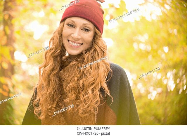 Portrait smiling woman in stocking cap under autumn trees