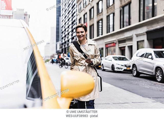 USA, New York City, smiling woman in Manhattan approaching a taxi