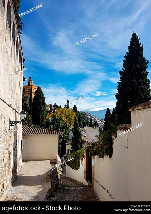 View of Granada street in the Realejo neighborhood with views of the Sierra Nevada and the Alhambra Palace. Andalusia, Spain