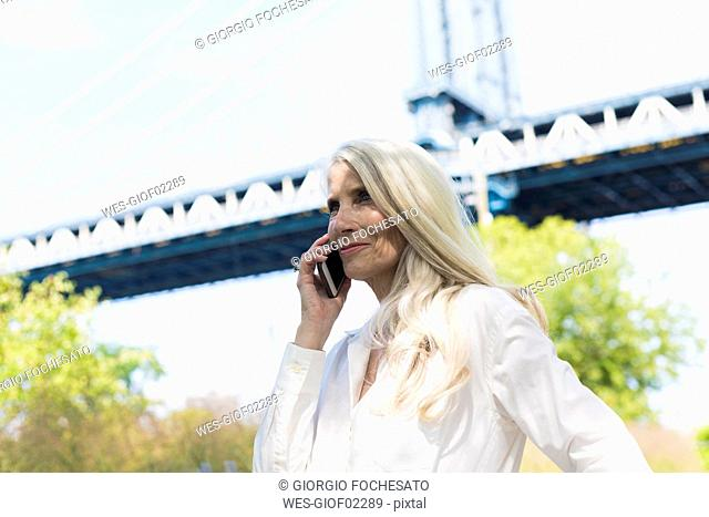 USA, Brooklyn, mature woman on the phone in front of Manhattan Bridge