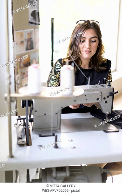 Portrait of young designer using sewing machine in her atelier