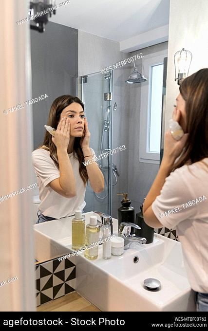 Woman checking make-up on face while standing in bathroom at home