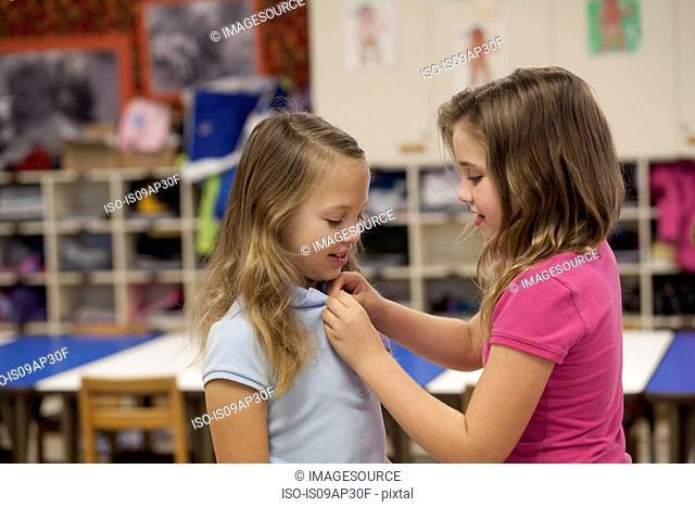 Girl buttoning friend's tee shirt in classroom