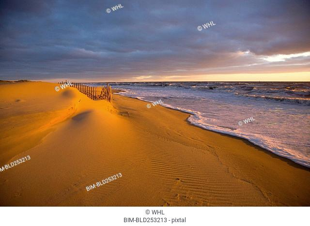 Ocean waves near sand dunes at sunset