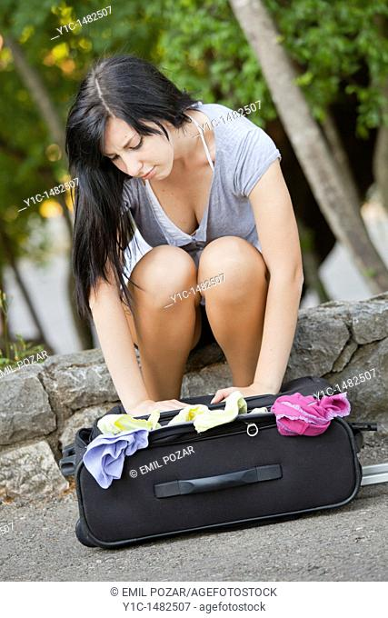 Attractive young woman is packing a travel suitcase