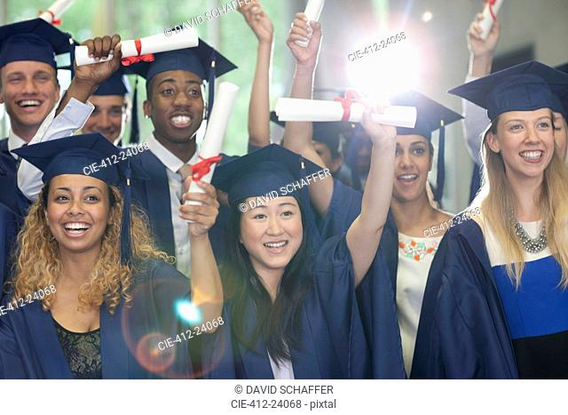 Smiling university students standing in corridor with their diplomas after graduation ceremony