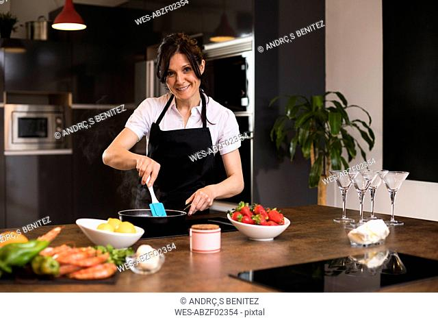 Portrait of smiling woman cooking in kitchen using a pan