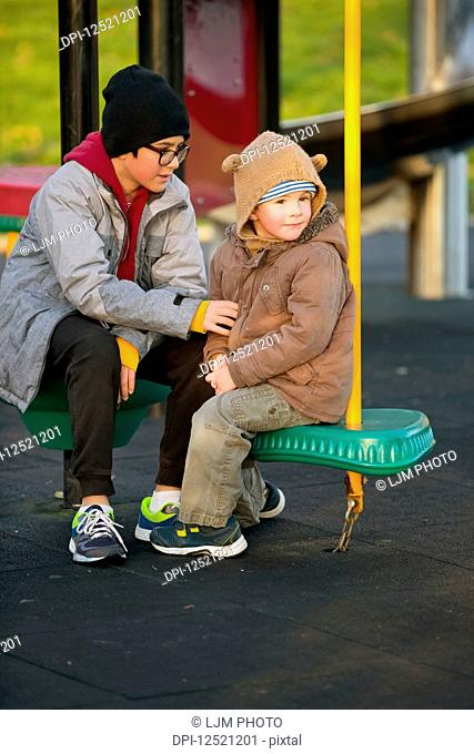 A young boy with his older brother sitting and talking at a playground; Langley, British Columbia, Canada