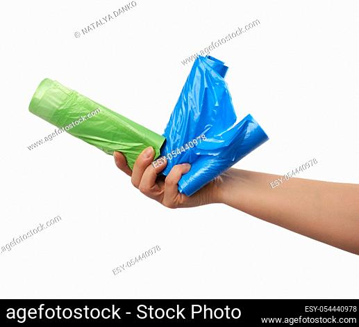 female hand holds a bundle of green and blue plastic bags for garbage, part of the body with the subject isolated on a white background