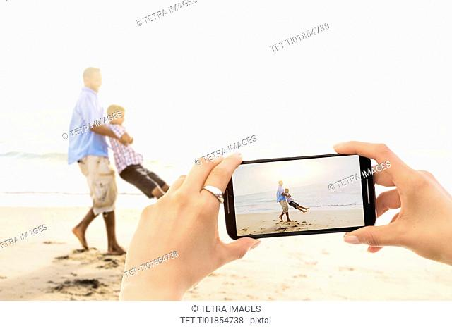 Young woman photographing father with son (12-13) on beach
