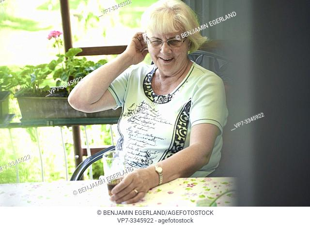 senior woman sitting at table outdoors in allotment garden