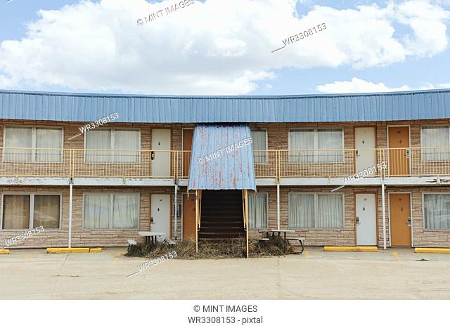 Abandoned motel building with a rusty metal awning, drawn curtains at the windows, and tumbleweed around the steps