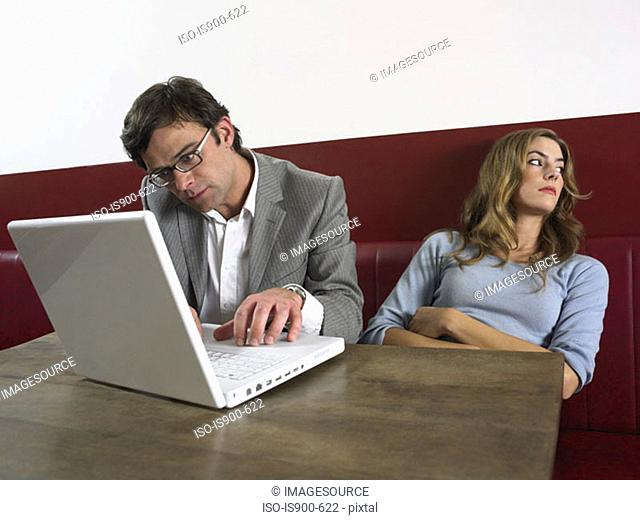 Woman bored as man works on computer