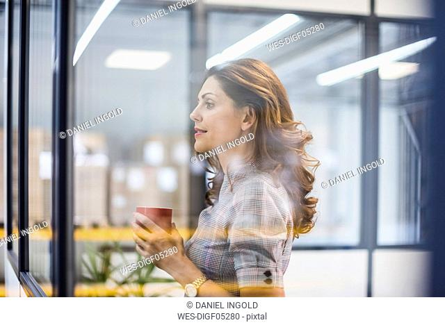 Pretty office worker standing in office, drinking coffee