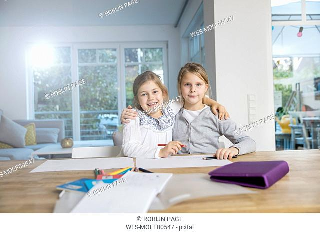 Portrait of two girls embracing doing homework at table together