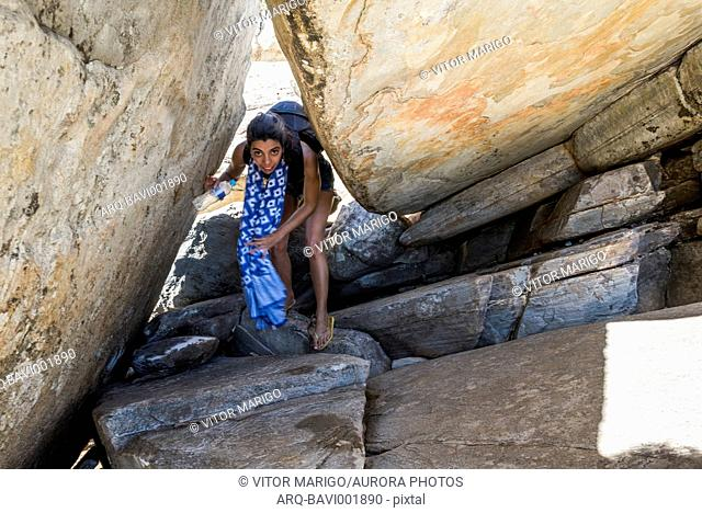 Front view of woman bending while hiking among rocks in Serra do Cipo National Park, Minas Gerais, Brazil