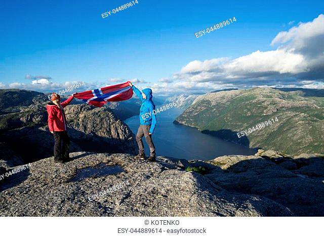 Pathway Preikestolen (Pulpit Rock). Couple with the flag of Norway. Panorama of the Lysefjord. Sunny weather in the mountains