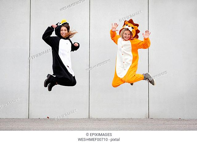 Two women in penguin and lion costume jumping in front of concrete wall
