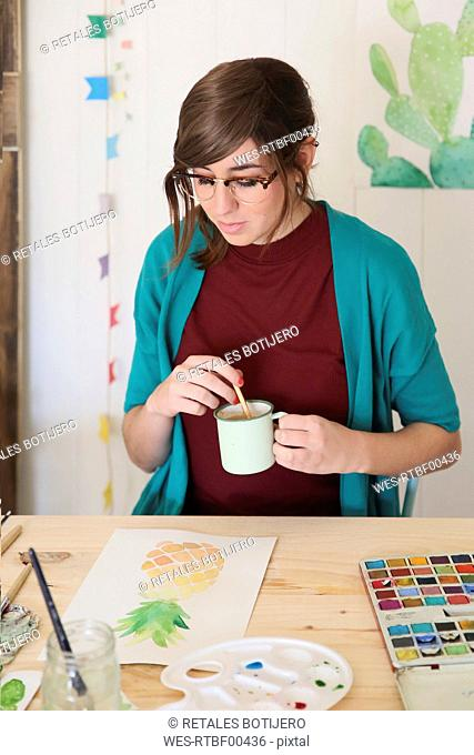 Painter looking at aquarelle of a pineapple at desk in the studio