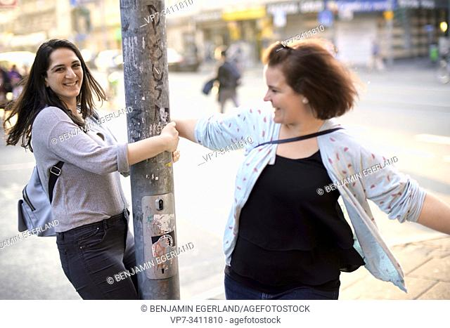 two lively friends dancing around street lamp post in city