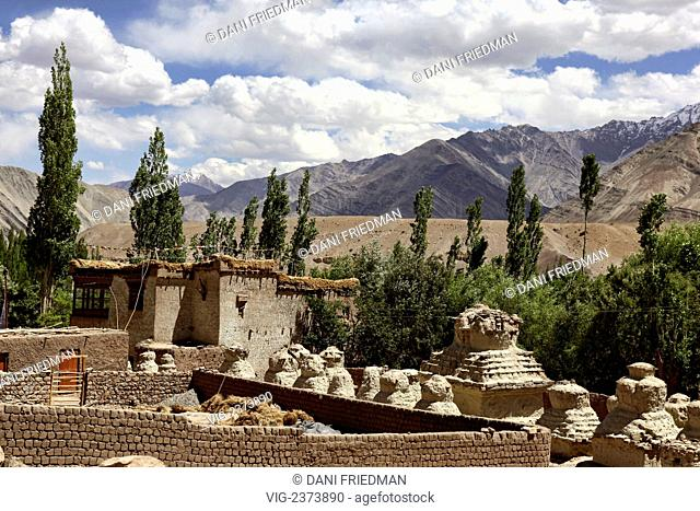 Buddhist chortens beside a typical Ladakhi mud brick home in Basgo, Ladakh. - BASGO, LADAKH, INDIA, 11/07/2010