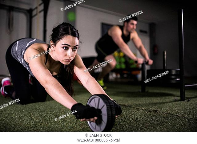 Crossfit training and fitness wheel pushups in gym