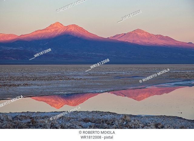 The profiles of two volcanos of the Cordillera de la Sal reflecting in a pool in the Desert of Atacama, Chile, South America