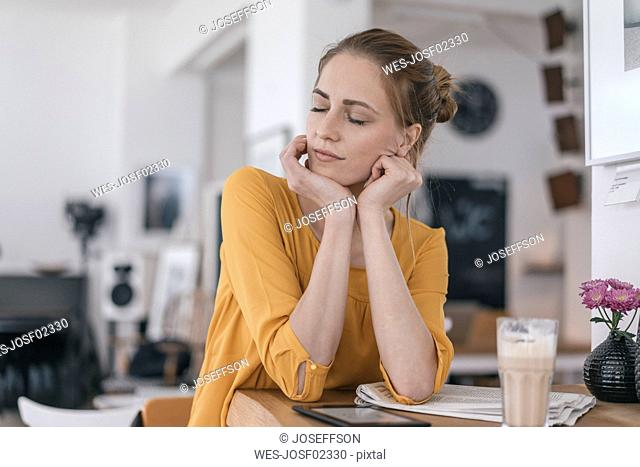 Young woman working in coworking space, closing eyes