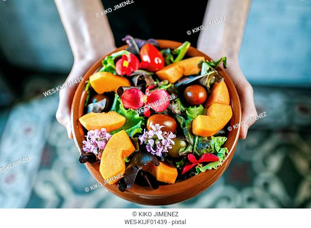 Man's hands holding bowl of mixed salad garnished with edible flowers, close-up