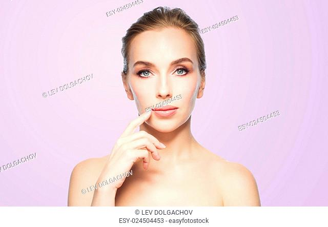 beauty, people and plastic surgery concept - beautiful young woman showing her lips over violet background
