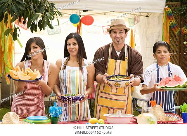 Hispanic family holding food at barbecue