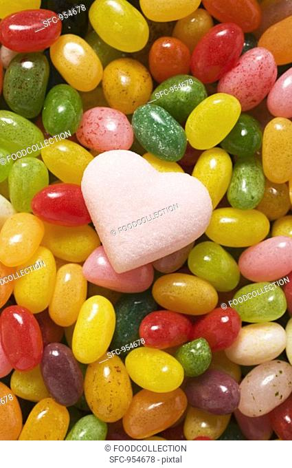 Coloured jelly beans & pale pink sugar heart full-frame