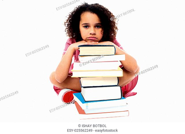 Tired schoolgirl resting her arms on books