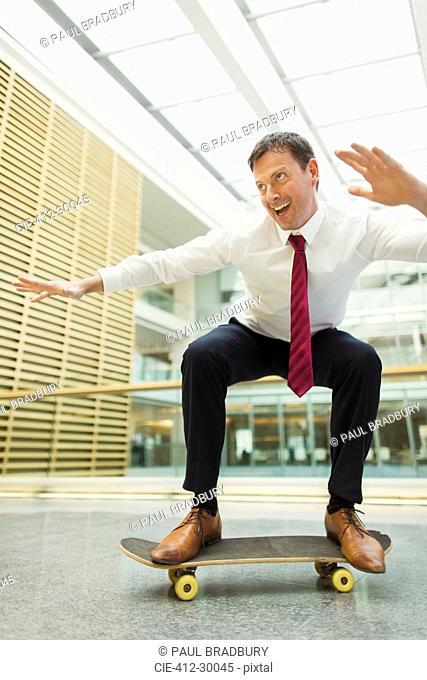 Playful businessman skateboarding in office
