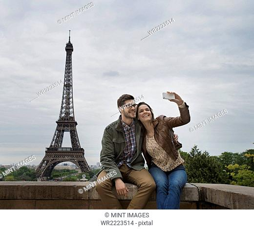 A couple seated side by side taking a selfy with the Eiffel Tower in the background