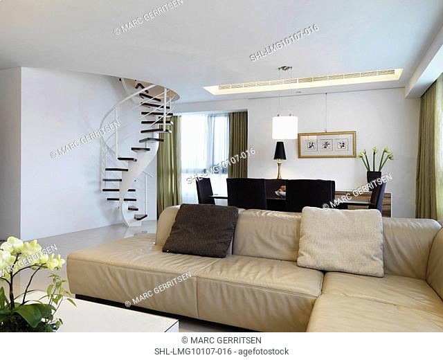 Beige leather sofa and spiral staircase in modern living room