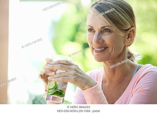 woman enjoying water with cucumber slices