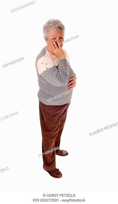 A older senior citizen woman standing isolated for white background.holding one hand on her face.