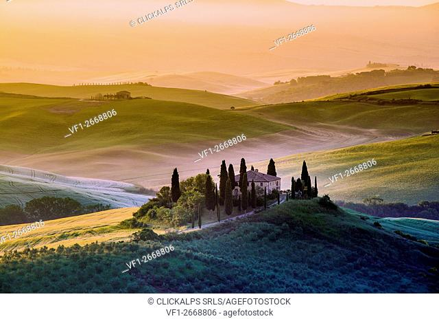 Val d'Orcia, Tuscany, Italy. A lonely farmhouse with cypress and olive trees, rolling hills