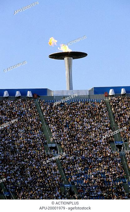 Olympic torch above a stadium