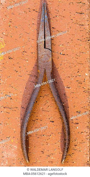 rusty tongs is is lying on stone ground
