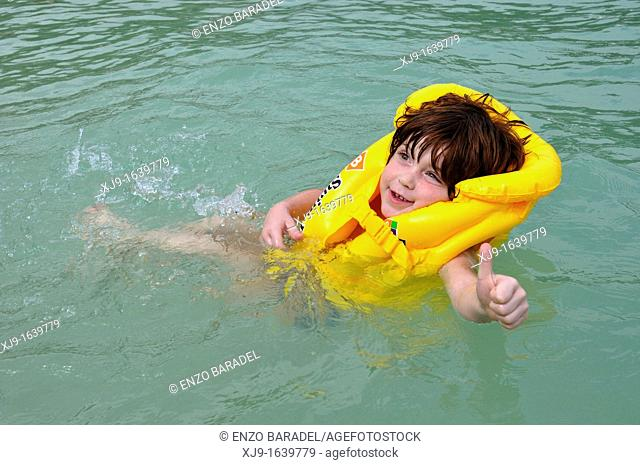 Child swimming with life jacket