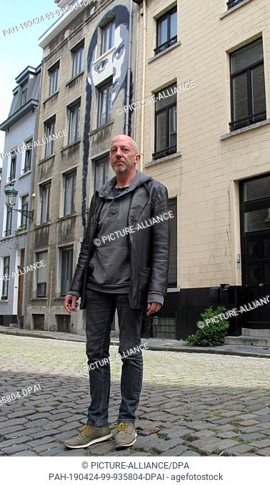 23 April 2019, Belgium, Brüssel: The Belgian artist Encq stands in front of a house on whose façade he has sprayed the face of the young Swedish climate...