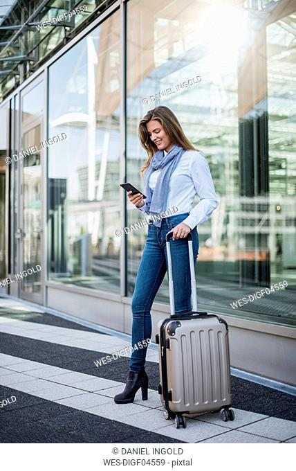 Smiling young businesswoman with suitcase looking at smartphone