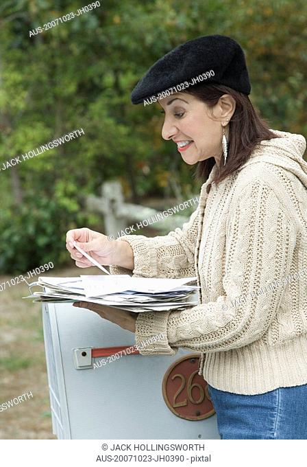Mature woman checking mails and smiling