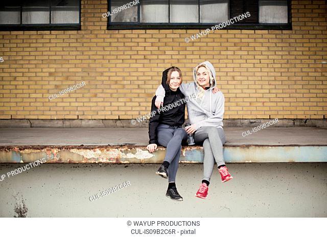 Portrait of two female runner friends sitting on warehouse platform