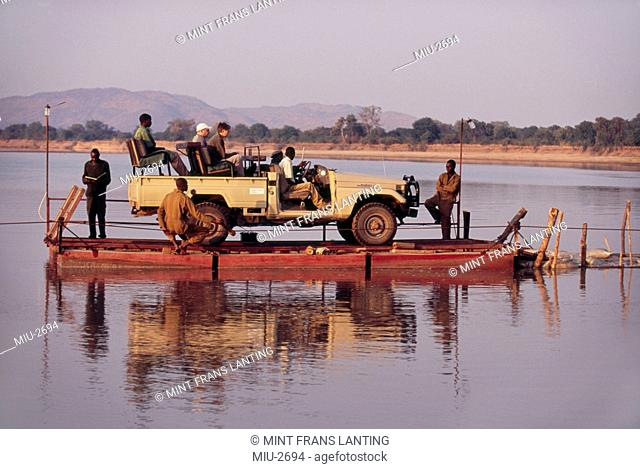 Safari vehicle crossing Luangwa River on pontoon, Zambia