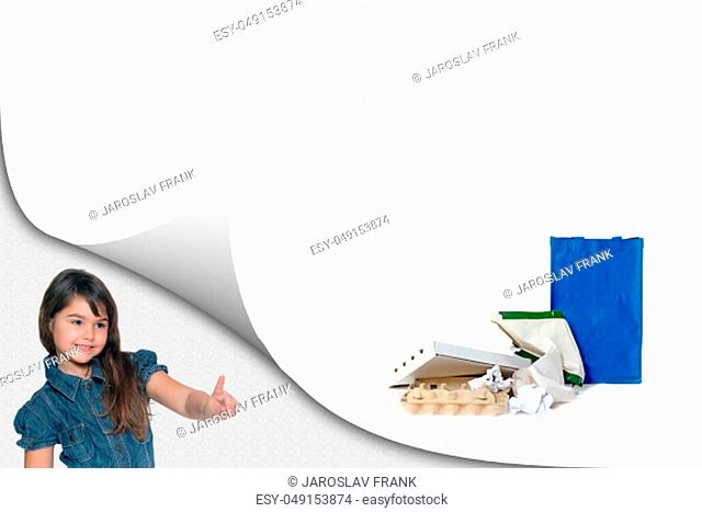 Cute little girl is showing a pile of sorted paper waste with ready blue bag on the white background ready for your text